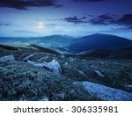mountain landscape. valley with stones in grass on top of the hillside of mountain range at night in full moon light - stock photo