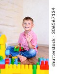 Small photo of Happy young boy playing with his building blocks holding a finished creation in his hands as he grins cheekily at the camera