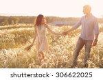 lovers walking in a field at... | Shutterstock . vector #306622025