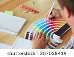 Small photo of Graphic designer choosing a color from the sampler