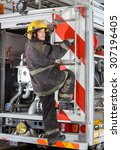 Small photo of Rear view portrait of young firewoman climbing truck at fire station
