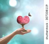 Small photo of Harmony living environment, ecological friendly concept with red heart tree and butterfly