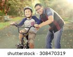 cute little boy try to ride a... | Shutterstock . vector #308470319