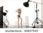 Young and sexy model posing in professionally equipped studio - stock photo