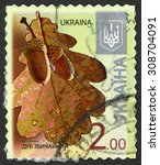 Small photo of UKRAINE - CIRCA 2014: post stamp printed in Ukraina shows oak tree leaf and acorn nut (quercus robur); 2kb brown, circa 2014
