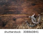 Stock photo two old rusty horseshoes with straw on vintage wooden board 308860841