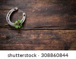 Stock photo st patricks day four leaved clover and a horseshoe on wooden board 308860844