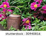 Bronze metal watering can in garden of beautiful, freshly watered flowers. - stock photo
