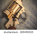 Small photo of Nagan revolver with cartridge on blue jeans background, close-up, part of. instagram image filter retro style
