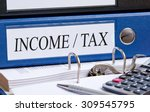 Small photo of Income and Tax - blue binder on desk in the office