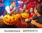 Stock photo jack o lantern on bar counter and friends on background 309592571