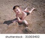 Boy on a beach having fun in sand - stock photo