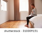 pregnant woman sitting on bed... | Shutterstock . vector #310309151