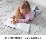 child reading book at home.... | Shutterstock . vector #310320629