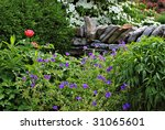 Garden scene with various flowers, greenery and section of stone fence.  Blooming dogwood trees in background. - stock photo