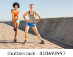 two young woman stretching... | Shutterstock . vector #310693997