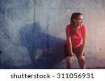 Stock photo young smiling female resting after an active fitness training while standing against gray wall with 311056931