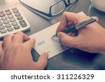 Small photo of Man writing a payment check at the table with calculator and glasses