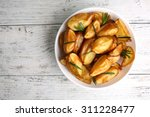 Baked Potato Wedges On Wooden...