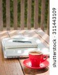hot coffee cup on wooden work... | Shutterstock . vector #311443109