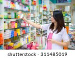 young female pharmacist picking ... | Shutterstock . vector #311485019