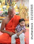 Small photo of Kanchanaburi, Thailand - July 22, 2013: Abbot of Wang Wiwekaram Temple, the most important and revered Buddhist temple in Sangkhla Buri district, is holding a cute young boy.