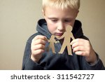confused child with cutting... | Shutterstock . vector #311542727