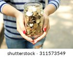 Woman Holding Money Jar With...