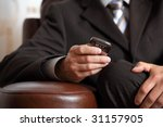 Text messaging or checking email on mobile phone whilst waiting for a business meeting - stock photo