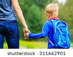 mother holding hand of little... | Shutterstock . vector #311662901