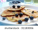 Blueberry pancakes with maple syrup.  Apple juice behind. - stock photo
