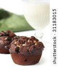 Chocolate-chip muffins with a glass of milk.  Shallow depth of field. - stock photo