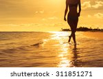 woman walking on the beach  | Shutterstock . vector #311851271