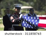 Marine Folds Flag At Memorial...
