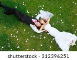 happy wedding couple lying on... | Shutterstock . vector #312396251