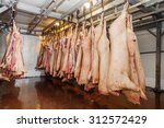 Small photo of Pig carcasses in a slaughterhouse or abattoir hanging from metal hooks on a rail in a cold room