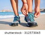 runner tying shoelaces on the... | Shutterstock . vector #312573065