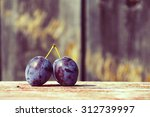 Two Plums On A Wooden Surface...