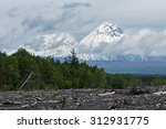 Small photo of Beautiful summery view on cone of active Klyuchevskoy Volcano (in the clouds) and Kamen Volcano on a cloudy day. Klyuchevskaya Group of Volcanoes, Kamchatka Peninsula, Russian Far East.