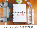 """Small photo of """"Adrenaline Rush"""" text on notebook with delicious green apple, measure tape, spectacle, a bottle of mineral water, and bodybuilding tools on wooden background - healthy, exercise and diet concept"""