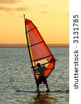 Backlit wind surfer at sunset on calm coastal water - stock photo