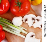 Fresh tomato,  green onion, sweet pepper and mushrooms on a board - stock photo