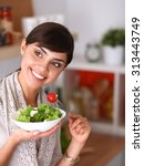 young woman eating fresh salad... | Shutterstock . vector #313443749