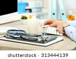 doctor working at table in... | Shutterstock . vector #313444139