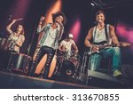 Small photo of Multiracial music band performing on a stage
