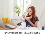 young woman eating breakfast... | Shutterstock . vector #313694351