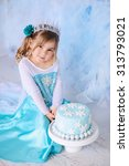 Small photo of Little princess girl on a styled Frozen birthday party with snowflakes cakes