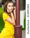 Small photo of Young beautiful woman in yellow dress has leant against lamppost