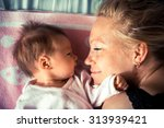 Newborn With Mother Looking At...