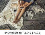 Stock photo beautiful woman model with coffee pastries home phone on the blanket with a cat 314717111